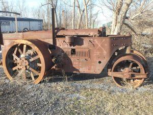 steamroller at rest on the roadside rusting away..