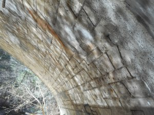 daydream play of sun off the water on the underside of the old stone bridge