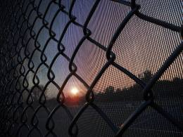 Sunset through the fence at the tennis courts...